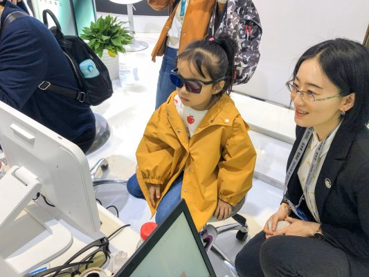 Yolanda LI, APAC Optometry Education Manager is helping a 5-year old girl to experience Eyeviz300.